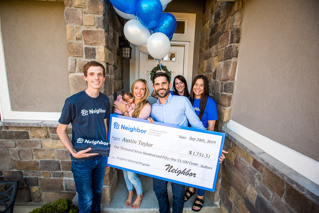 Austin Taylor, the top referrer for the month of August in Neighbor's mortgage payment referral program, joins his family to accept a check from Neighbor equal to one month's mortgage payment.
