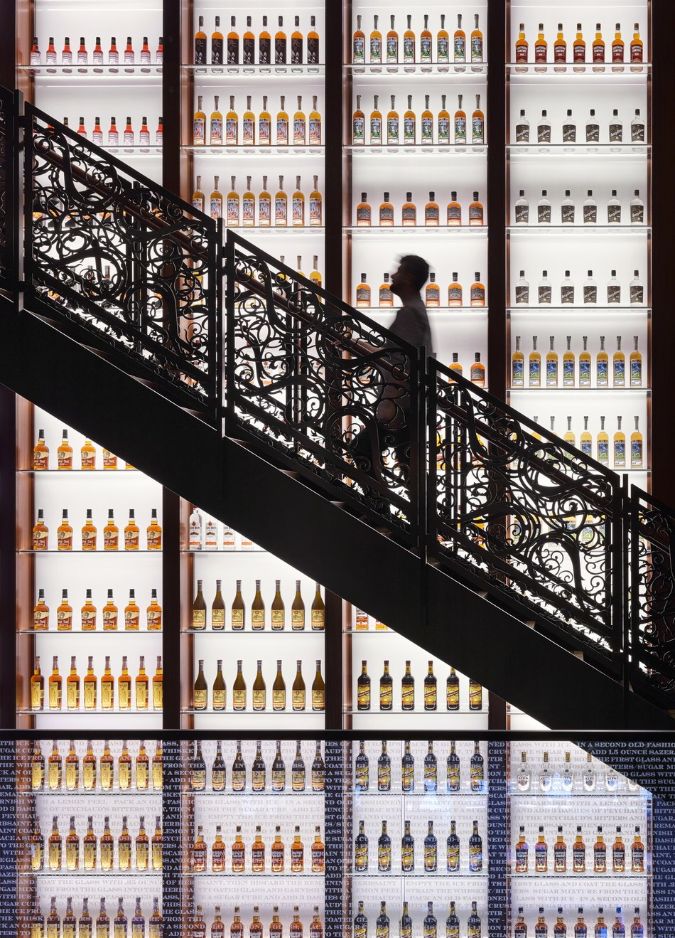 "Detail of staircase and bottle wall. Contemporary methods and materials evoke the spirit of 1880s architecture and reveal the historic character of the buildings while making clear what's new. The three-story display wall featuring Sazerac bottles is back-lit to draw the attention up through the building and to the upper floors. Plasma-cut steel panels with cutout ""S"" shapes and star anise flowers take inspiration from the brand. Architecture by Trapolin-Peer Architects. ©️ Alan Karchmer/OTTO"