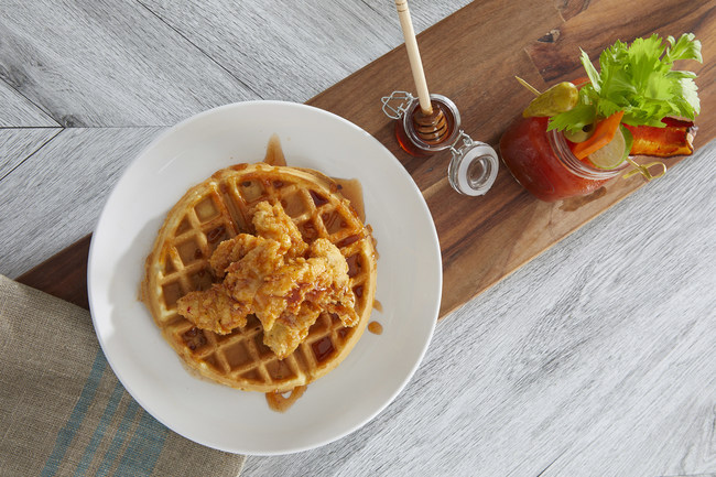 Another Broken Egg Cafe Chicken & Waffles next to the ABE Famous Infused (Bloody) Mary. This brunch dynamic duo brings the spice with a house-made chipotle honey syrup drizzle and pepper-infused vodka.