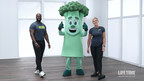 Two smiling personal trainers stand next to a happy broccoli mascot with its thumbs up
