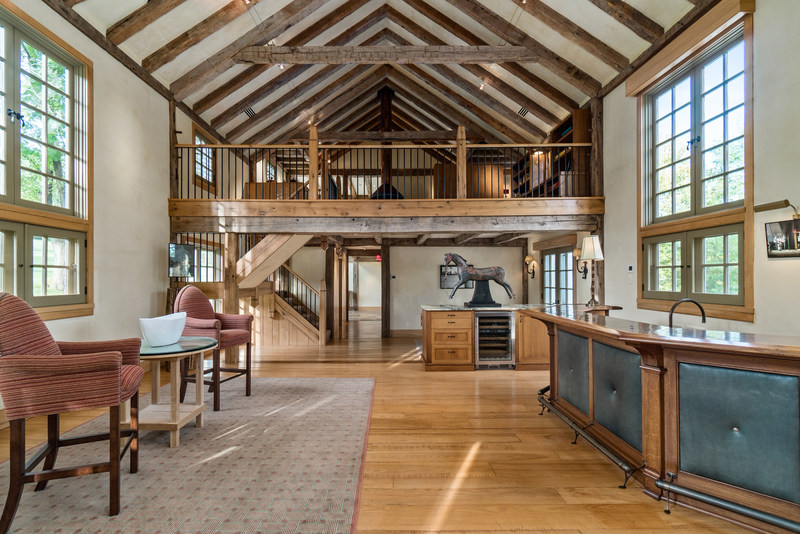 Interior living spaces of the barn include multiple areas for recreation and entertainment, such as the open-plan living room with wet bar (pictured here). The third-level recreation room offers a central, wood-burning fireplace and a large screen TV set in a handsome cabinet that swivels to allow viewing from multiple seating areas. NewJerseyLuxuryAuction.com.