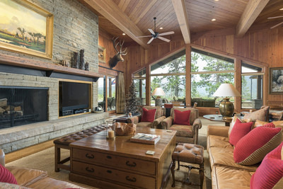 The open-plan residence boasts spacious entertaining spaces, many of which are ornamented with sandstone fireplaces, exposed beams, and walls of windows designed to maximize the awe-inspiring views of the surrounding land. DurangoLuxuryAuction.com.