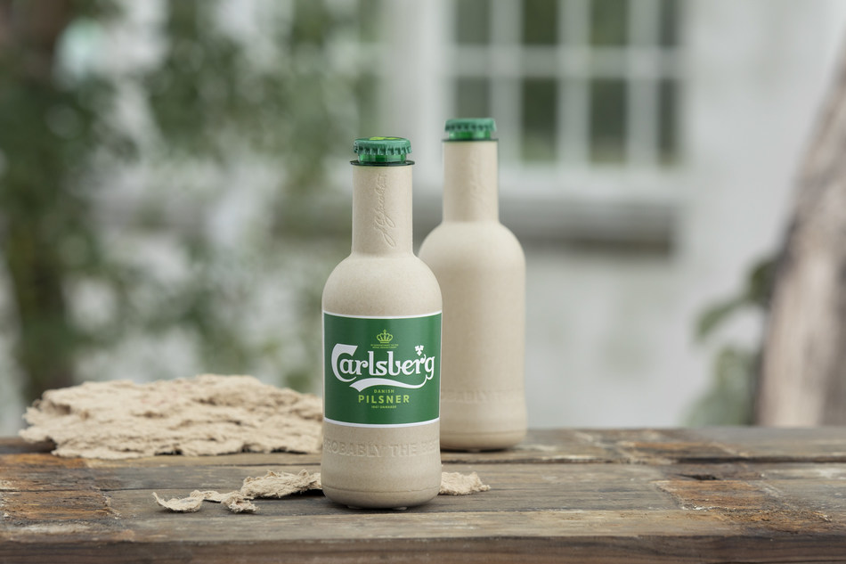 Carlsberg moves a step closer to creating the world's first 'paper' beer bottle. Pictured are the two new research prototypes for Carlsberg's Green Fibre Bottle, which both contain beer for the first time and are shown alongside the sustainably-sourced wood fibre they're made from.