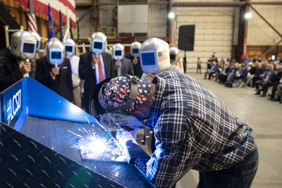 A welder authenticates the keel of LCS 27, the future USS Nantucket, by welding the initials of ship sponsor Polly Spencer.