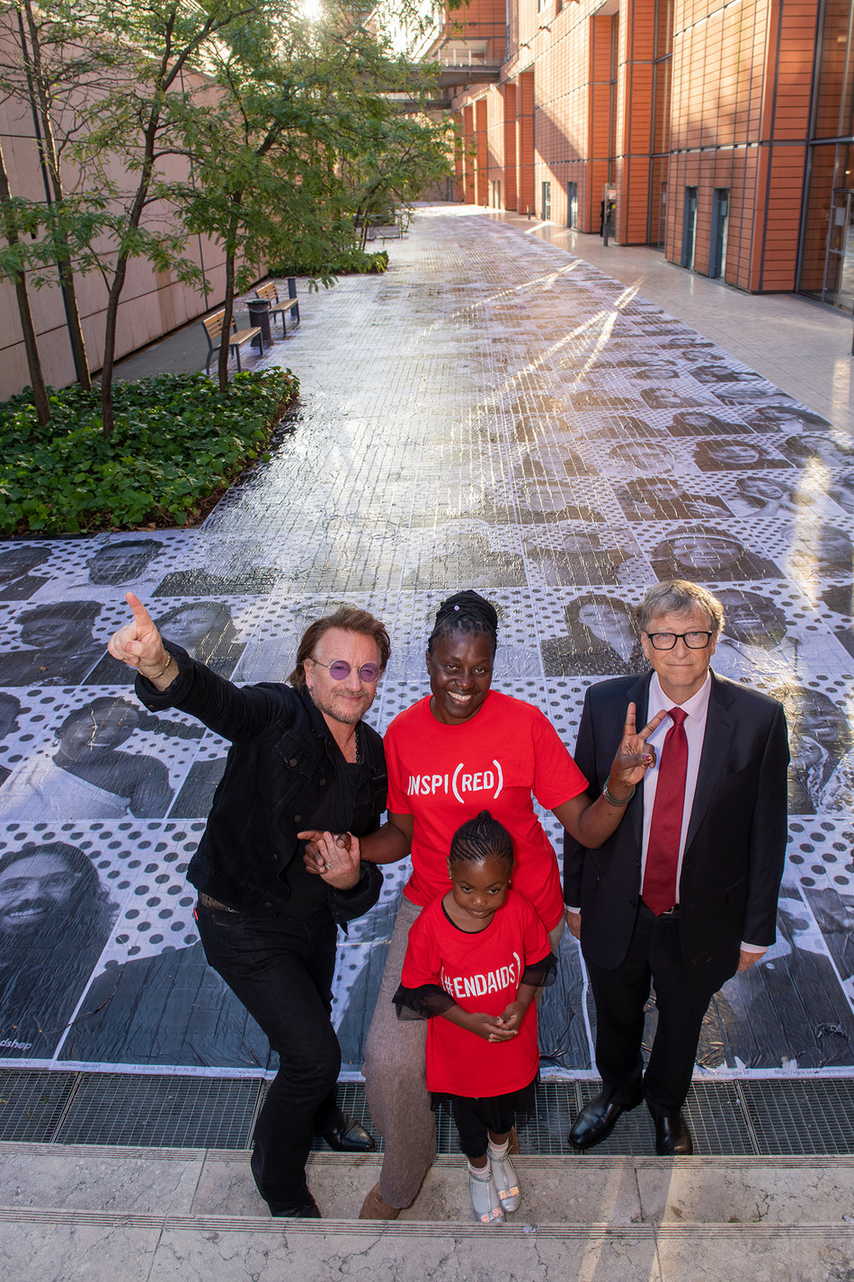 Bono, Co-Founder, (RED), AIDS activist Constance Mudenda, alongside her daughter, Lubona and Bill Gates, Co-Chair, the Bill & Melinda Gates Foundation, are photographed at an installation by the Inside Out Project in Lyon. The installation features the faces of 850 people who support the fight to end AIDS - the same number of women who contract HIV each day.