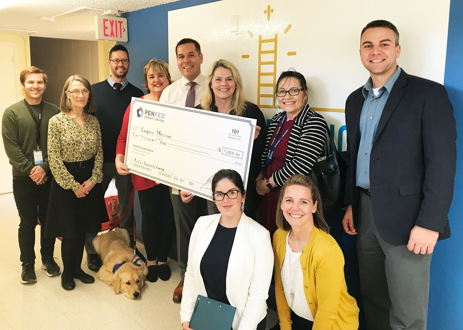 PenFed Credit Union employees and Journey, PenFed's Northwest Battle Buddies service-dog-in-training, present a donation check to the Eugene Mission.