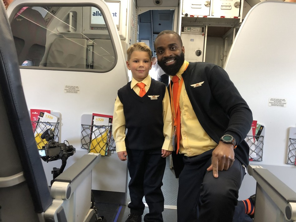 "Stephen ""SJ"" Awwad, honorary Allegiant flight attendant for a day, shows off his crew uniform."