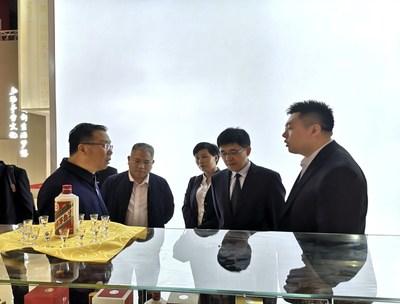 O presidente da Moutai, Li Baofang (primeiro, à esquerda), e o gerente geral, Li Jingren (segundo, à direita), visitam o estande da Moutai e recebem informações detalhadas sobre os produtos.