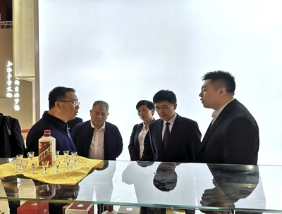 Moutai Chairman Li Baofang (1st L), Moutai General Manager Li Jingren (2nd R) visit Moutai exhibition booth and learn detailed information of products.