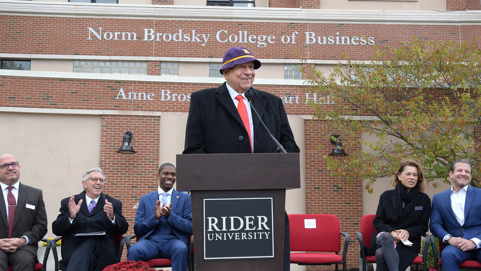 Norm Brodsky '64 speaks at the ceremony unveiling the Norm Brodsky College of Business, wearing the purple and gold beanie customarily worn by Rider freshmen of his day.
