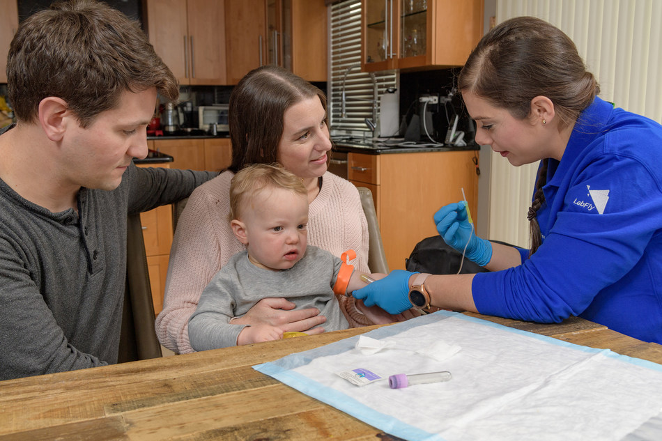 Northwell Health Labs Phlebotomist Dina Durdu (far right) prepares a blood draw for a toddler in the privacy and convenience of his own home with mom and dad by his side. Credit Northwell Health.