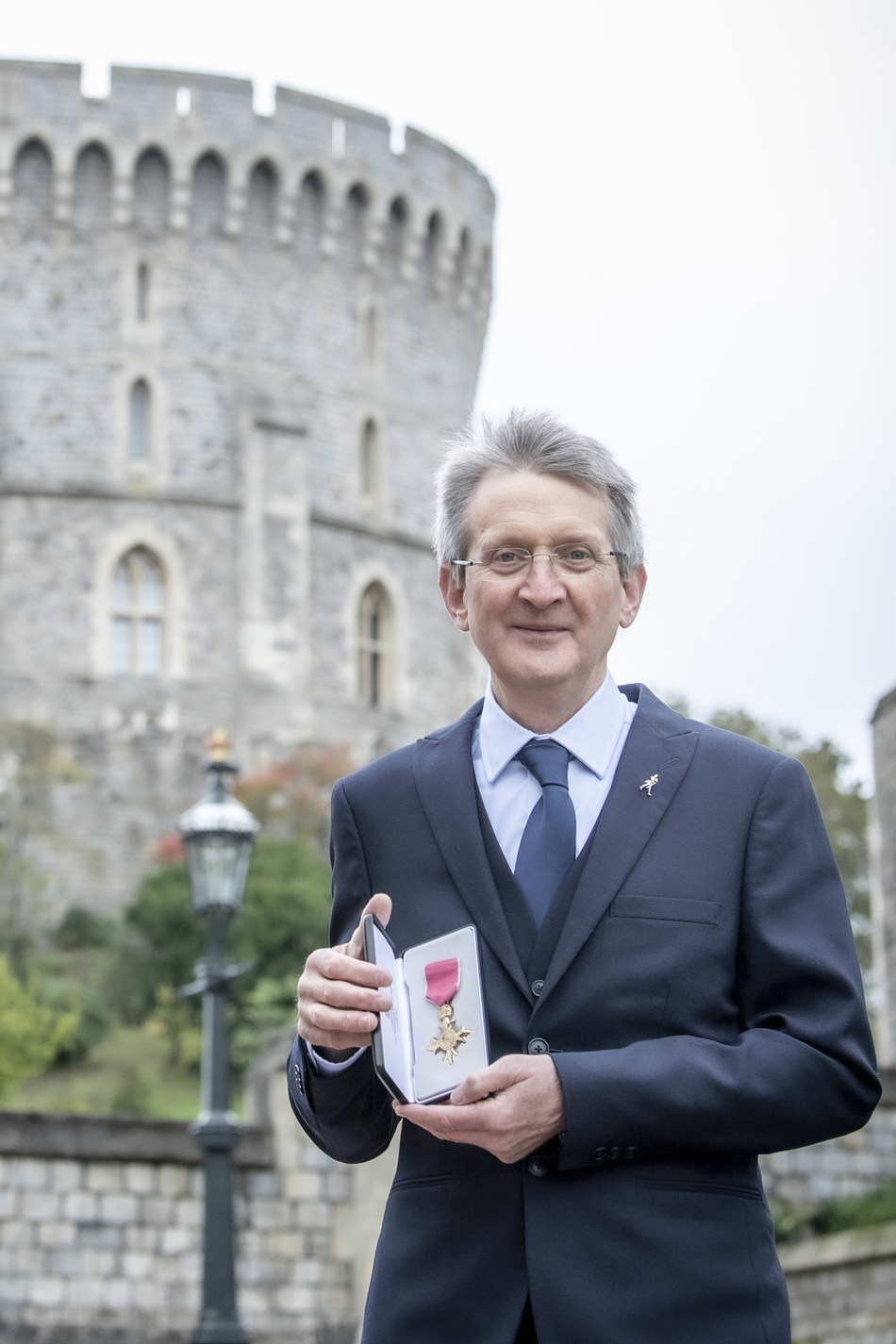 Dr. Jim Beveridge with his OBE award outside Windsor Castle.