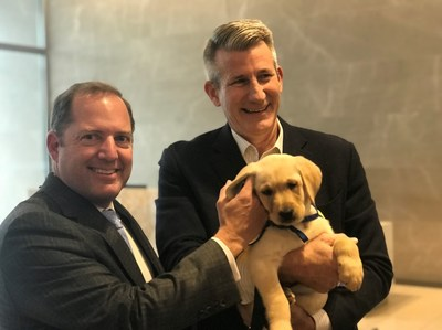 "PenFed Credit Union CEO and President and PenFed Foundation CEO James Schenck and PenFed Foundation President John ""Mick"" Nicholson greet WestPoint, the newest member of the PenFed team from Canine Companions for Independence as he reports for his first day of duty."