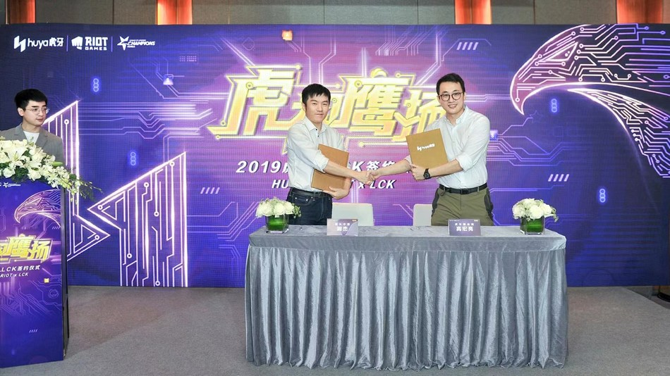 HUYA Vice President Gao Hongliang signs agreement with Zhou Jie from Riot Games China