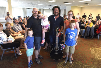 Leah (in the middle) with her family and Paul Langlois (right) from The Tragically Hip, at her wish reveal in Kingston, ON. in July 2019 with Pita Pit Canada. (CNW Group/Pita Pit Canada)
