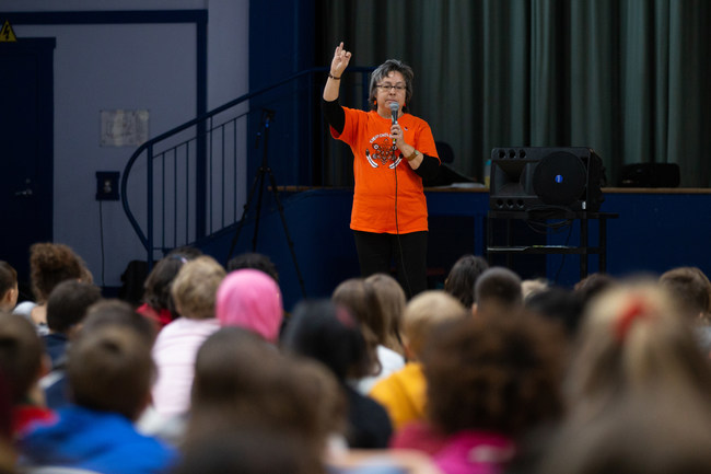 Phyllis Webstad of the Orange Shirt Society, tells her story to elementary students at the Paths to Reconciliation National Tour launch. Photo: Ben Powless/Canadian Geographic (CNW Group/Royal Canadian Geographical Society)