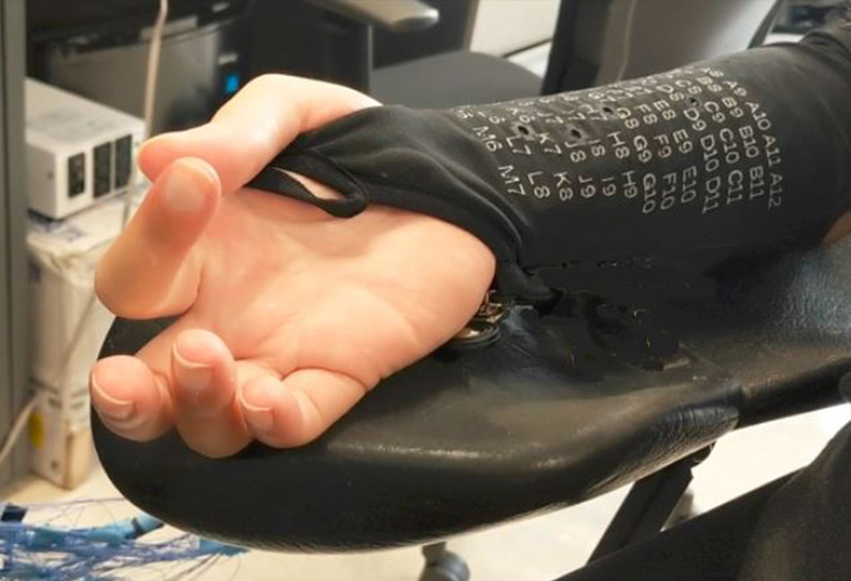 An over-the-skin bioelectronic sleeve used to help individuals with paralysis move their fingers.