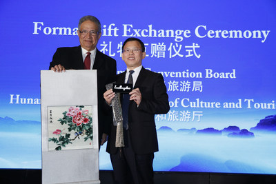Ernest Wooden Jr. and Xianchun Chen exchanging gifts characterized with local cultures