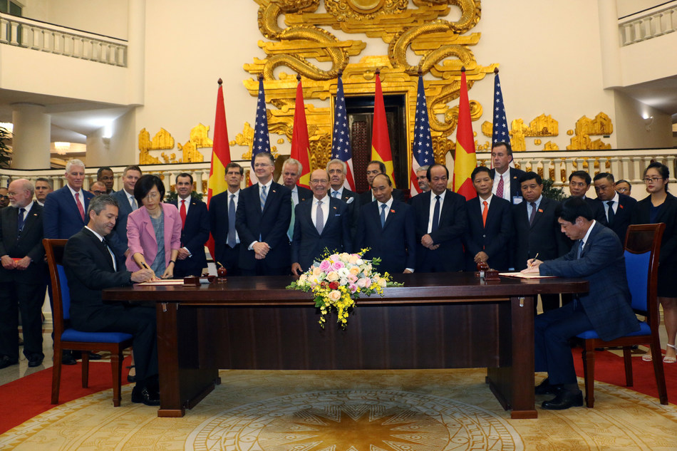 Cem Tanyel, executive vice president and president, Sabre Airline Solutions, and Trinh Hong Quang, executive vice president, Vietnam Airlines, sign an agreement in the office of the Prime Minister of the Socialist Republic of Vietnam. The ceremony was held in the presence of Prime Minister Nguyen Xuan Phuc; Wilbur Louis Ross Jr., United States secretary of commerce; and representatives from both countries.
