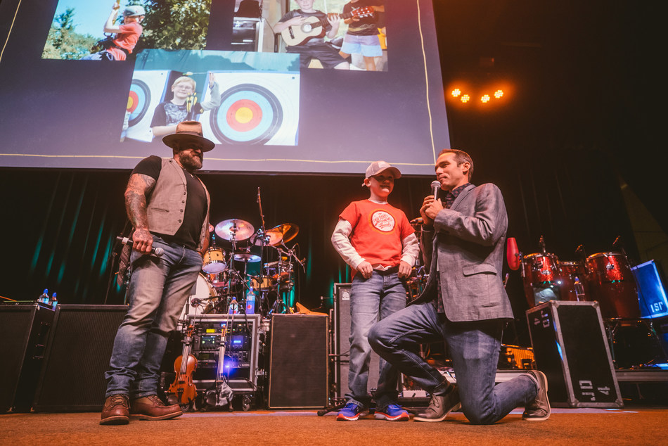 Zac Brown and Camp Director Scott Hicok talk to  Brody A., summer camp alum.