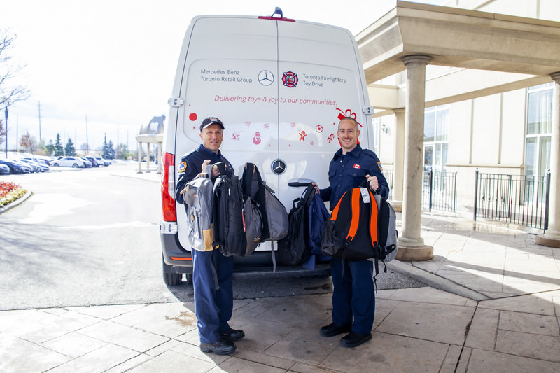 President of the Toronto Firefighters' Toy Drive Rick Berenz (L) joined his son, firefighter Geoff Berenz (R) to collect toys and load them into a Mercedes-Benz Sprinter Cargo van (CNW Group/Mercedes-Benz Canada Inc.)