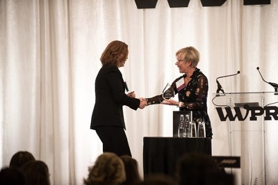 2018 WWPR Woman of the Year Award winner Wendy Hagen, President of hagen, inc, presents Maura Corbett, Chief Executive Officer and Founder, Glen Echo Group, with the 2019 WWPR Woman of the Year Award.