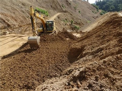 Excavator scarifying the Coffer dam surface prior to compaction. The surface was sealed with a smooth drum compactor due to impending rainfall. (CNW Group/TVI Pacific Inc.)
