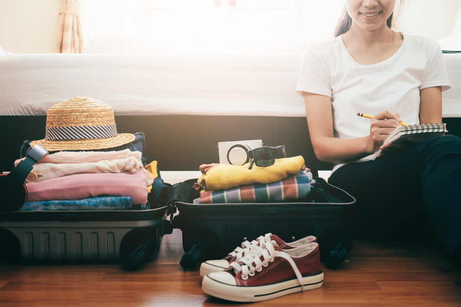 Preparation for vacation or travel. Packing her clothes and stuff into a large open suitcase that is almost already full. (CNW Group/FlightHub)
