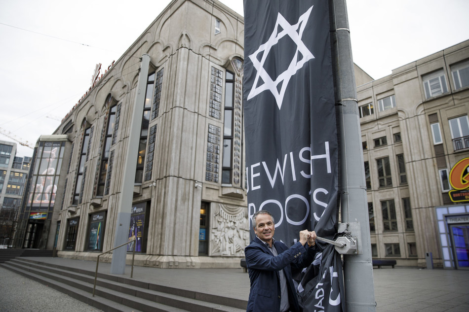 """""""We want to set up a sign of solidarity for Jewish life in Germany,"""" says Director Dr Berndt Schmidt hoisting a commanding flag which features the Star of David and the inscription 'Jewish Roots Since 1919' in front of the Friedrichstadt-Palast in Berlin on Wednesday 27 November 2019."""