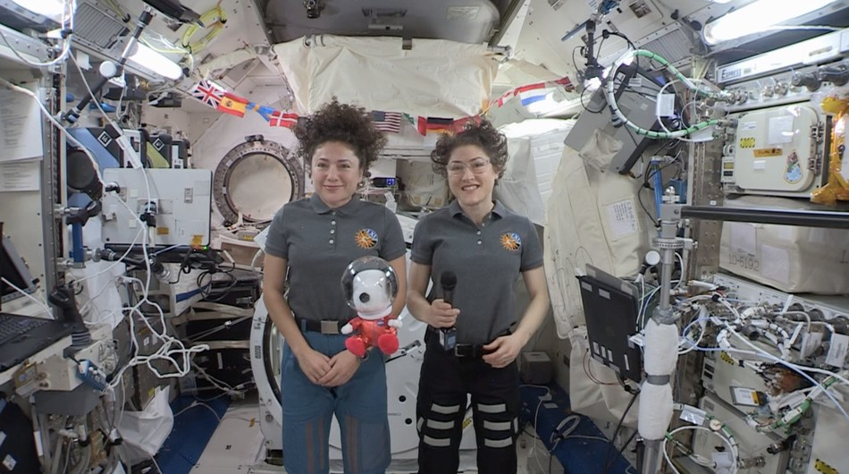 """World-Famous Beagle Snoopy—in 8-Inch Plush Form—Was """"Floating On Air"""" with Astronauts Christina Koch and Jessica Meir as They Sent Greetings from the International Space Station to Millions of Macy's Parade Viewers, While a New 49-Foot Tall Astronaut Snoopy Macy's Parade Balloon Soared Over Manhattan. (CNW Group/DHX Media Ltd. (dba WildBrain))"""