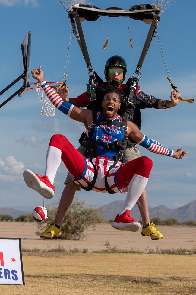 In celebration of the fourth annual World Trick Shot Day, Harlem Globetrotters star Hammer Harrison successfully completed the highest slam dunk ever attempted, skydiving from 13,000 feet in Eloy, Ariz.