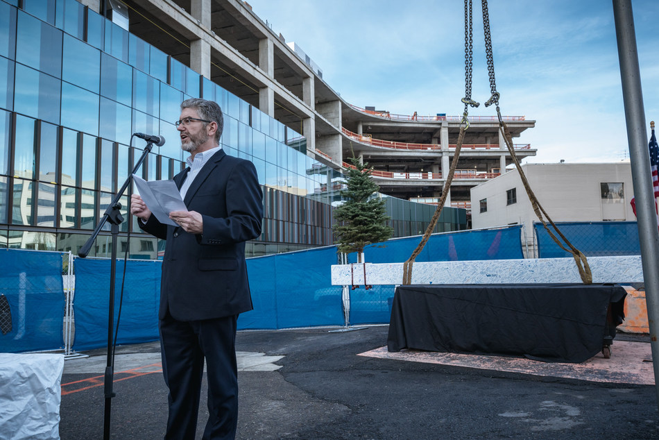 With the New East Tower standing behind him, Overlake Medical Center's Chief Operating Officer Thomas DeBord addresses the audience that gathered for the building's ceremonial topping out.