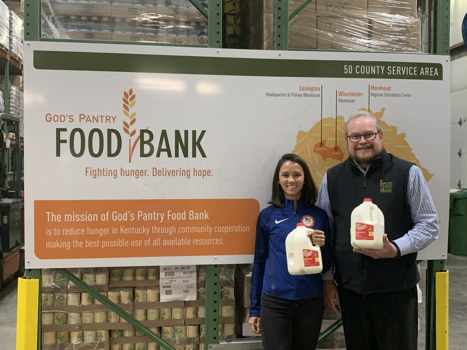 Lee Kiefer (left) a U.S. Olympic fencer and Lexington native, donates a year's worth of milk to God's Pantry Food Bank. Michael Halligan, food bank CEO was on hand to help accept the donation.
