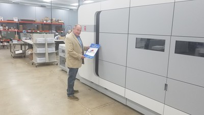 Larry Kuhlman admires output from the Océ VarioPrint i300 – a poster recognizing Graphic Village's contributions to the Sisters of Notre Dame de Namur