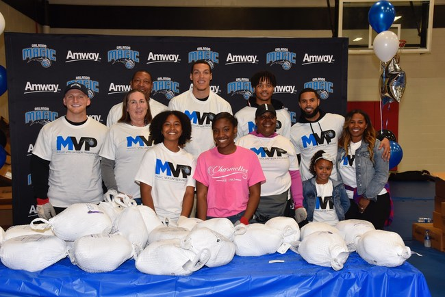 Magic players Aaron Gordon, D.J. Augustin, Markelle Fultz and their families join Amway Corporation distributing turkeys and all the trimmings to the community before Thanksgiving. Photo by Gary Bassing.