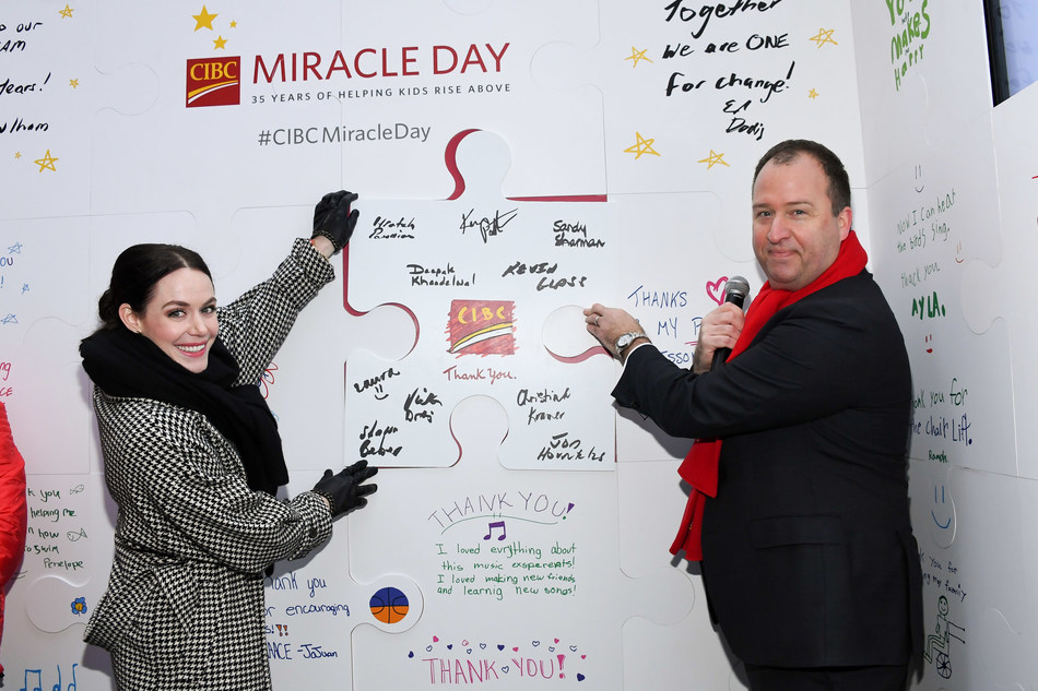 Olympic ice dance champion Tessa Virtue and Ed Dodig, Executive Vice President and Head, Private Wealth Management Canada and CIBC Wood Gundy, unveil giant thank-you card in Toronto to mark 35th anniversary of CIBC Miracle Day. (CNW Group/CIBC)