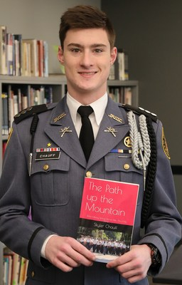 1CPT Skyler Chauff of St. John's Northwestern Military Academy, located in Delafield, WI, poses with his memoir detailing the benefits he's derived from his military high school experience.