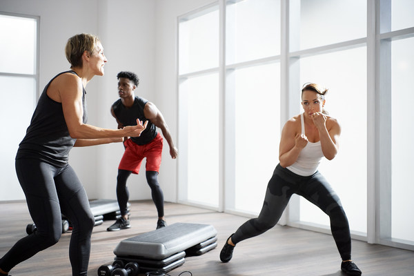 An instructor leads two people through Life Time's Ringside group fitness class
