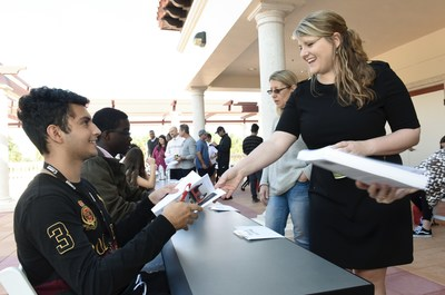 Danny Soto, a student at Olympic Heights Community High School in Boca Raton, Florida, signs a copy of Show, Don't Tell for Andrea Shue, Canon Solutions America's Segment Specialist, during the Future Authors Project event at Spanish River Library.