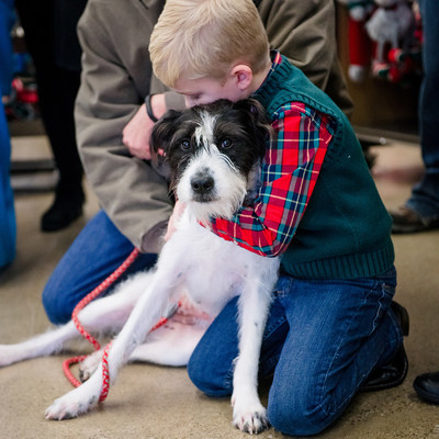 Elliott hugs adopted dog, Bindy, after it's revealed that their story helped Little Victories Animal Rescue Group in West Virginia win a $5,000 grant award.