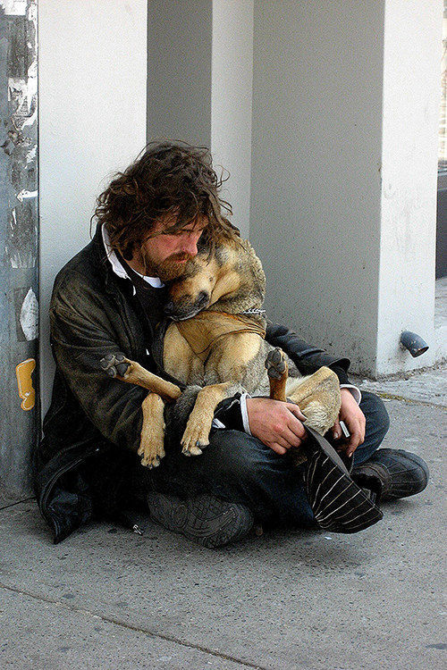 A homeless man bonds with his dog.