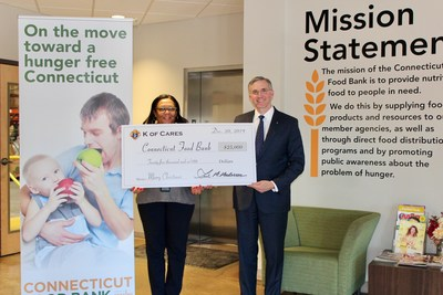 Connecticut Food Bank CEO Valarie Shultz-Wilson accepts a ceremonial check from Knights of Columbus Deputy Supreme Knight Patrick Kelly on Friday, Dec. 20 at the food bank's Wallingford facility.