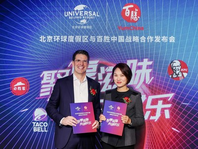 Page Thompson, President and Chief Operating Officer - International of Universal Parks & Resorts and Joey Wat, Chief Executive Officer of Yum China exchange the partnership agreement