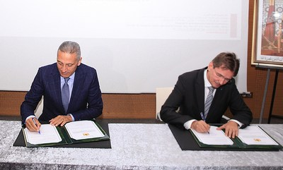 On the left H.E. Moulay Hafid Elalamy (The Minister of Industry, Trade, Green and Digital Economy) and the right Mr. Andreas Höfer (Regional Executive Vice President India, Middle East, Africa & Asia Pacific at TÜV Rheinland) during signing the contract.