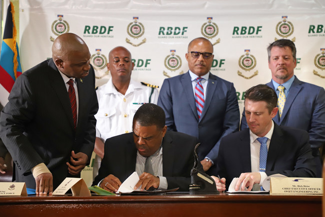 The Ministry of National Security Bahamas Unmanned Aerial System (BUAS) held a contract signing with Swift Tactical Systems at HMBS Coral Harbour Base. Eugene Poitier, Ministry of National Security Permanent Secretary and Rick Heise, Swift Tactical Systems President and CEO are pictured signing the contract.