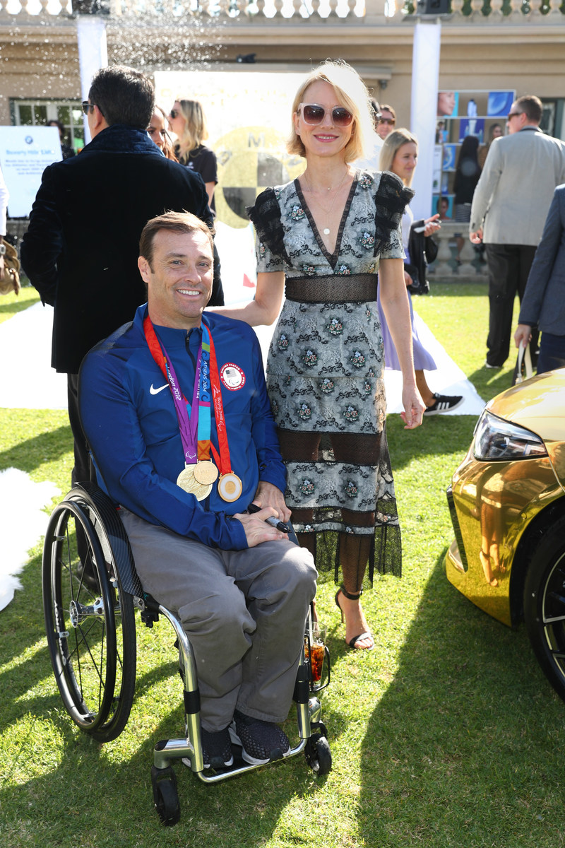 Actress Naomi Watts and Paralympian Tennis Player David Wagner bond near the BMW Beverly Hills gold-dipped M8 at the 7th Annual Gold Meets Golden Event, presented by Coca-Cola, BMW Beverly Hills and FASHWIRE.