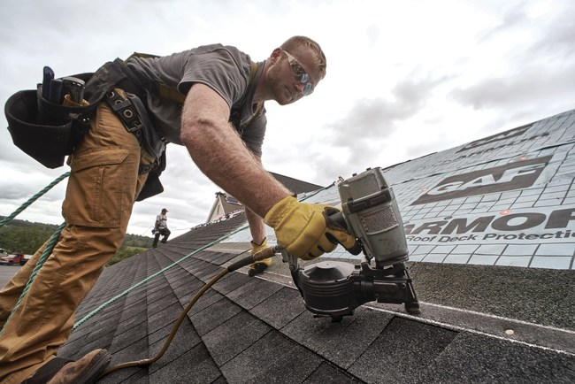 A roofing contractor installs new GAF Timberline® HDZ™ roofing shingles with ease and accuracy thanks to StrikeZone™ nailing area.