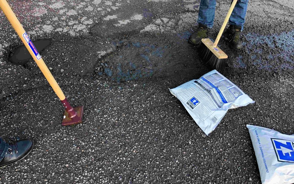 A small crew with a few bags of EZ Street Asphalt repair a pothole. The process of permanent repair is a 1-2-3 process: just sweep, fill, and compact. It even works in water and is guaranteed permanent.