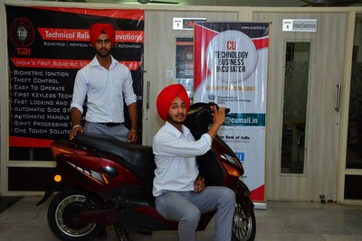 Automobile Engineering students of Chandigarh University, Khushwinder Pal Singh and Vikramjit Singh showing their newly developed Biometeric security kit installed on a two-wheeler.