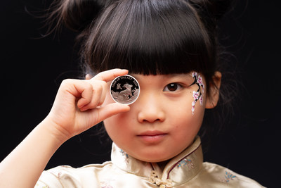 Catriona Lee, aged 9, presents The Royal Mint's latest Chinese zodiac coin from the Shēngxiào Collection, depicting the Lunar Year of the Rat to celebrate Chinese New Year on Saturday.